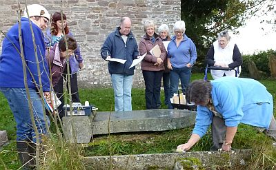 Eirwen Jones (far left) and Alison Noble (far right) advise the Llanddew group on how to identify gravestones prior to recording the inscriptions.